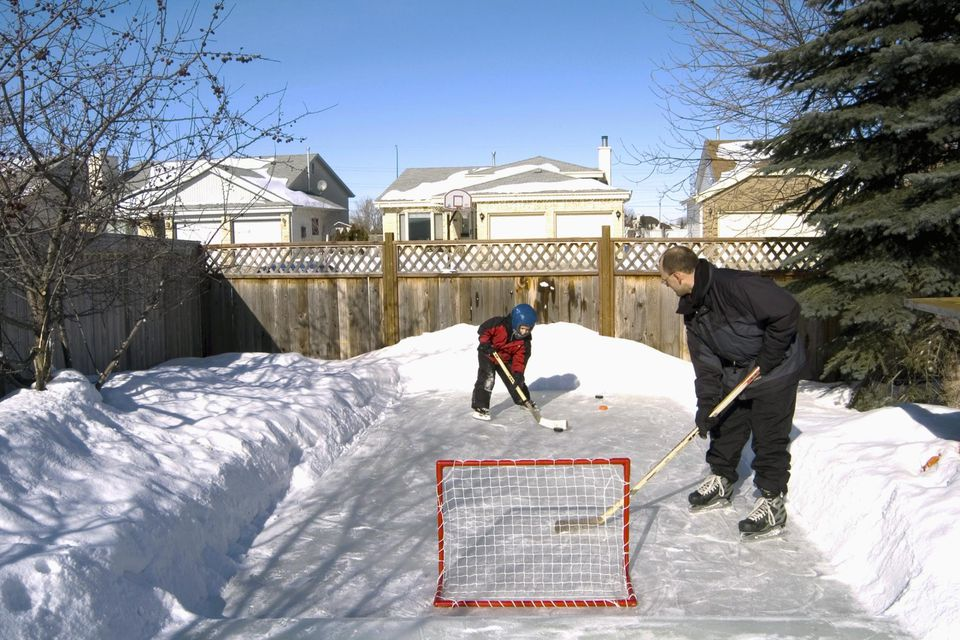 Father and Son Playing Hockey in Backyard, Winnipeg, Manitoba