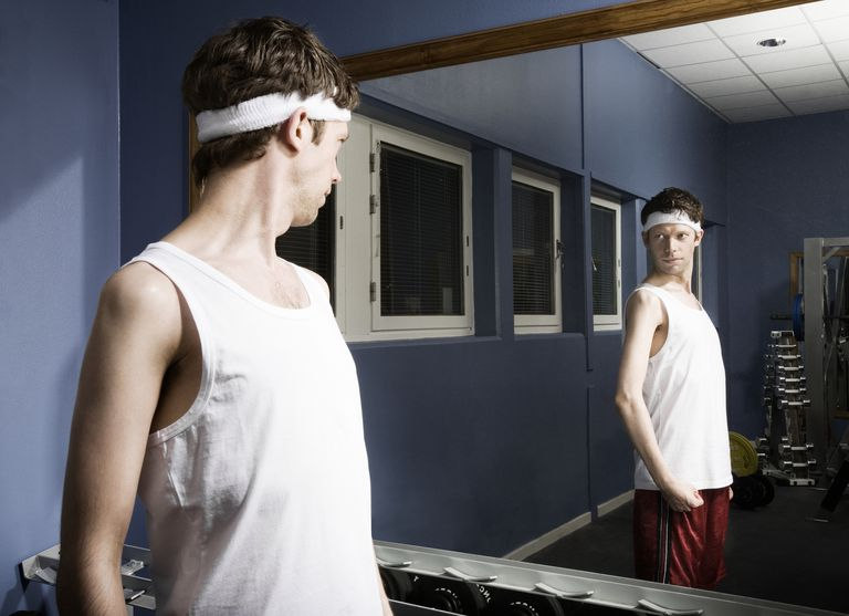 Man wearing sweatband looking at reflection in gym mirror, flexing arm