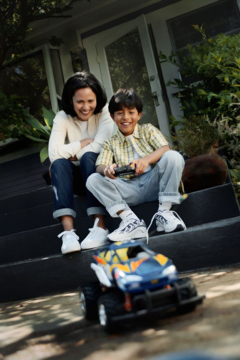 Mother and son (6-7) sitting on steps, looking at toy car