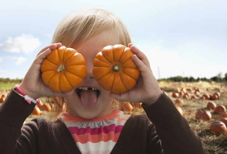 Girl with two pumpkins. She doesn't know about tax loss harvesting rules yet.