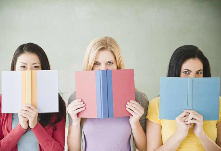 women looking out from behind books