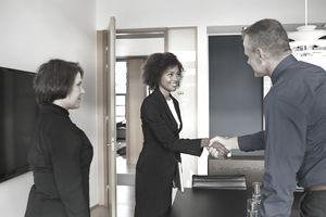Businesspeople making handshake at job interview