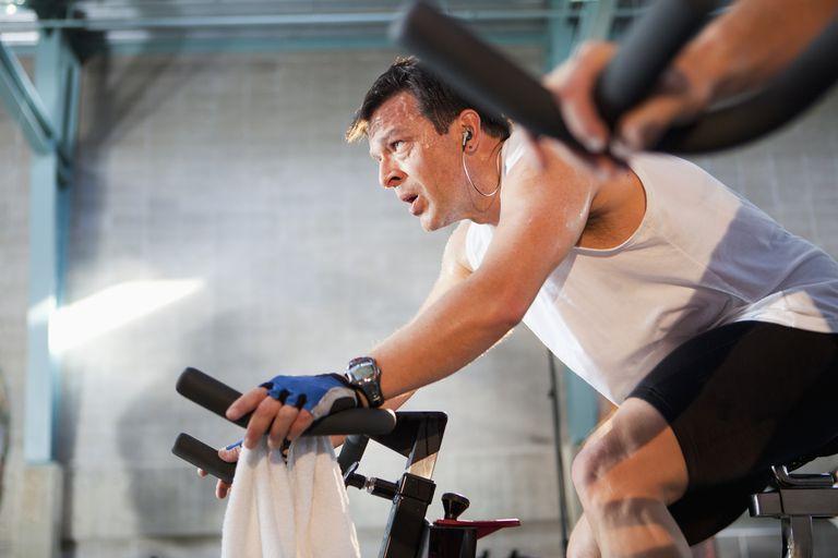 Hispanic man on exercise bikes in health club