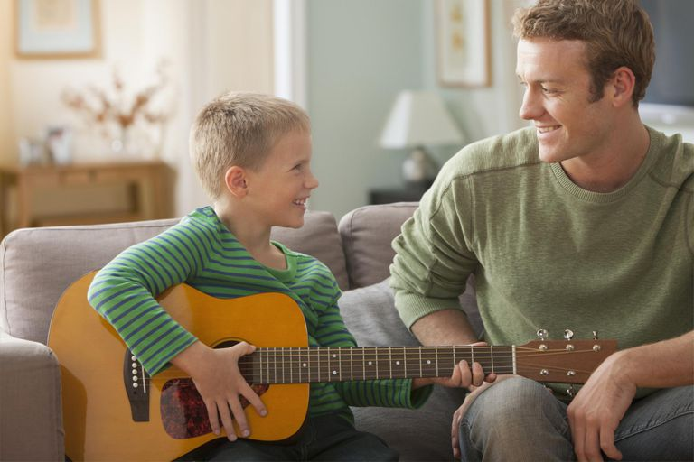 Caucasian father watching son play guitar