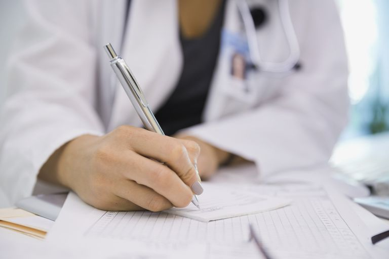 A doctor fills out a prescription.