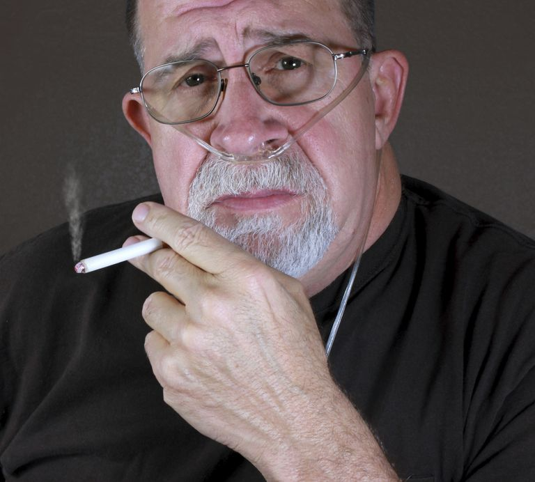 photo of a man smoking with an oxygen tube in his nose