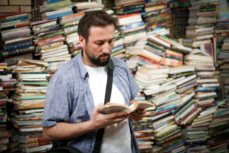 Hombre leyendo un libro en la biblioteca de libros antiguos