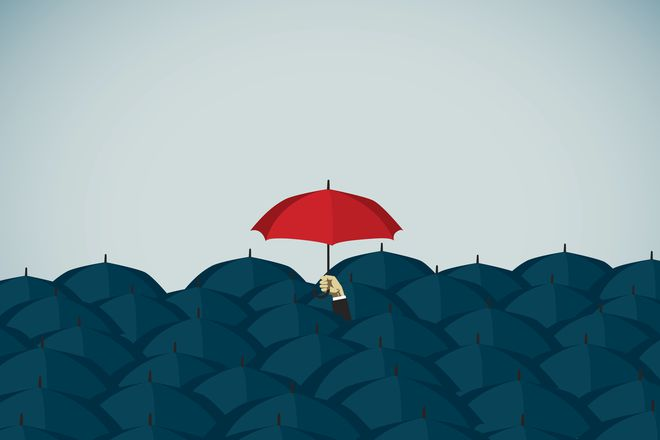 Man holding red umbrella overhead, symbolizing insurance