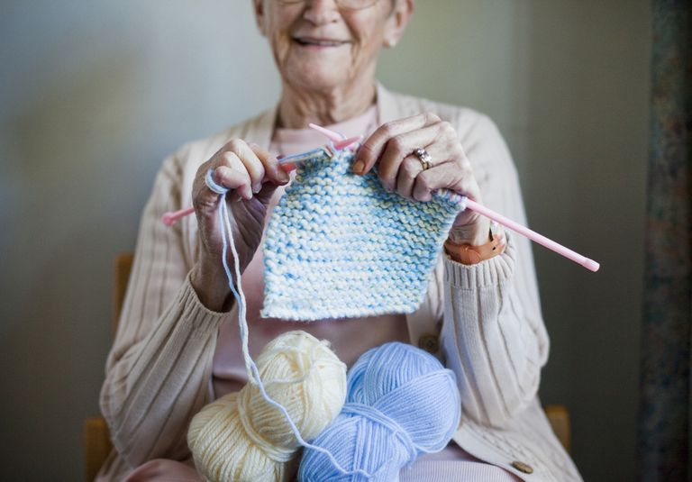 Older woman knitting with plastic needles