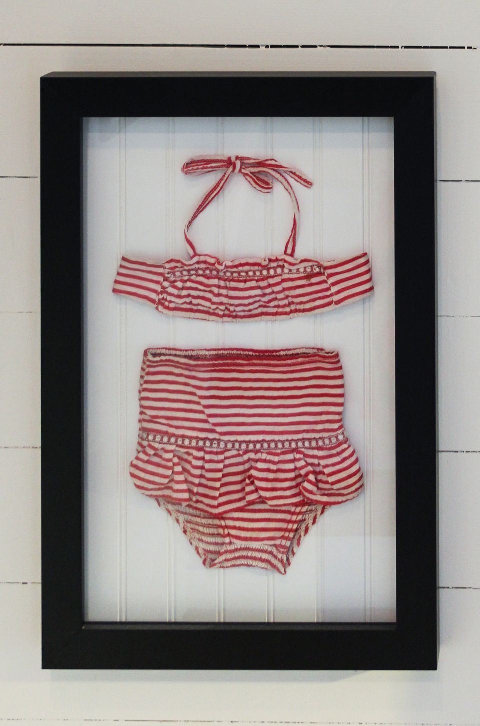 Vintage swimsuit framed and hanging on a wall.