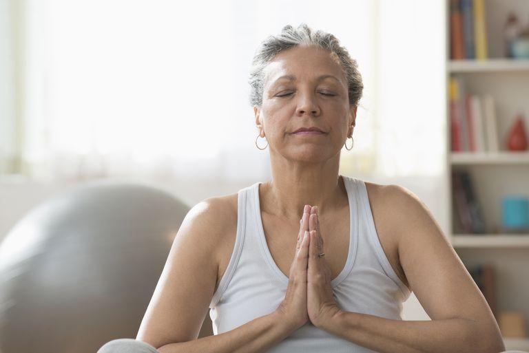 Older Hispanic woman meditating in living room