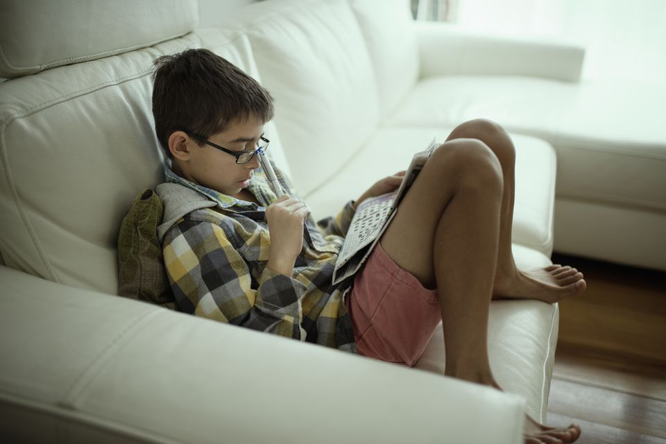 A kid filling out a crossword puzzle