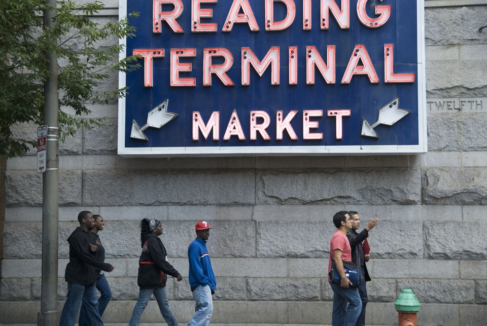 Pedestrians walking past neon sign of Reading Terminal Market.