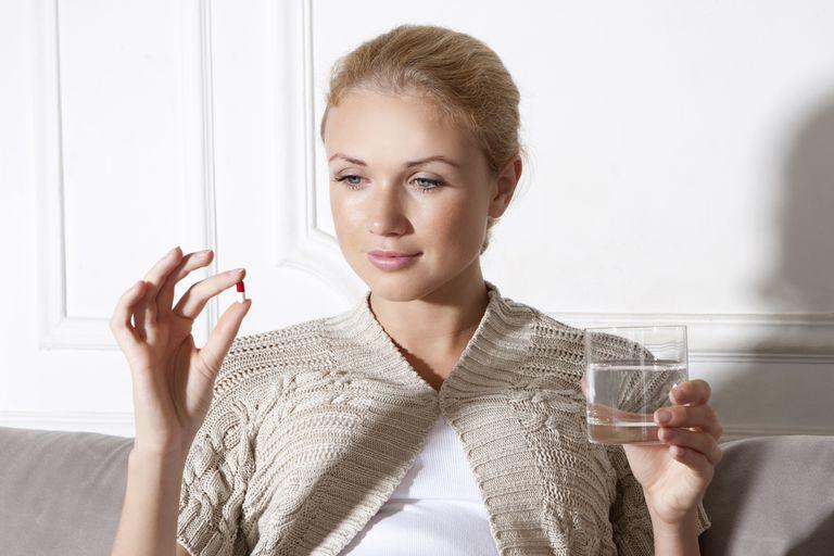 Smiling woman taking medication