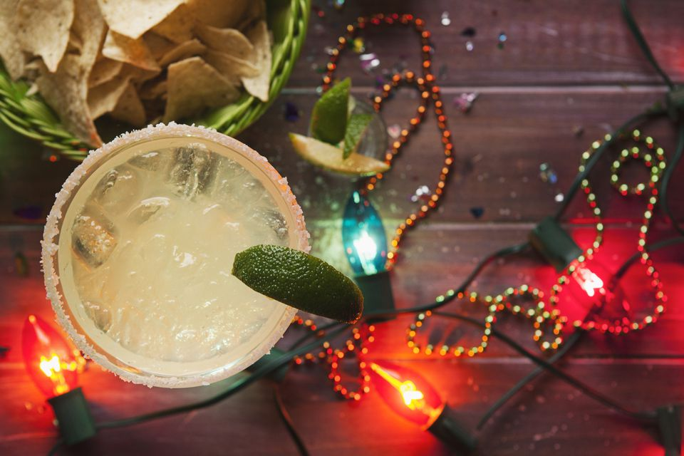 Margarita with lime in glass, nachos and fairy lights for Cinco De Mayo party