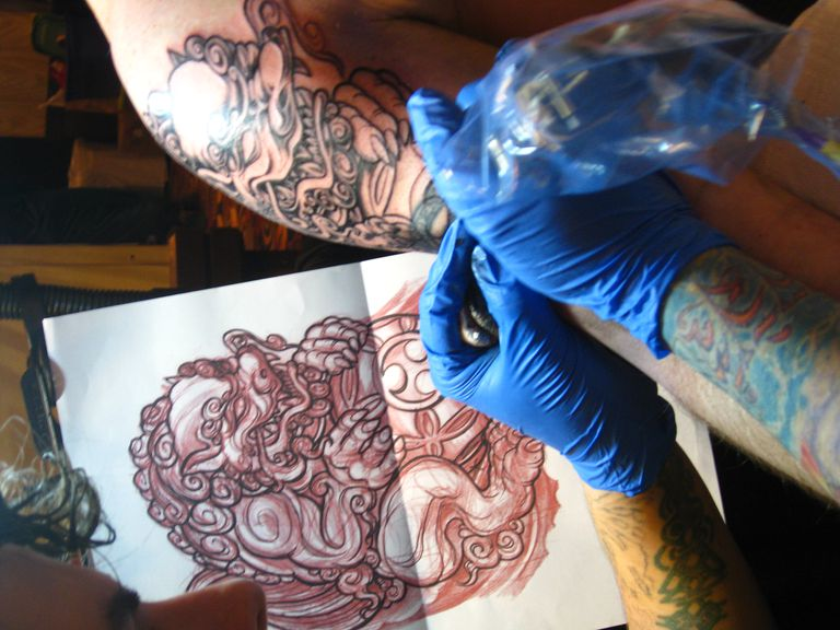 An artist tattooing a foo dog