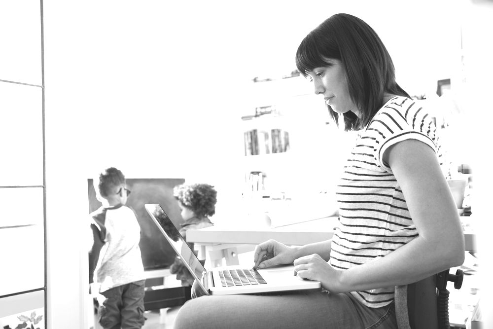 mother using laptop with two young kids in background