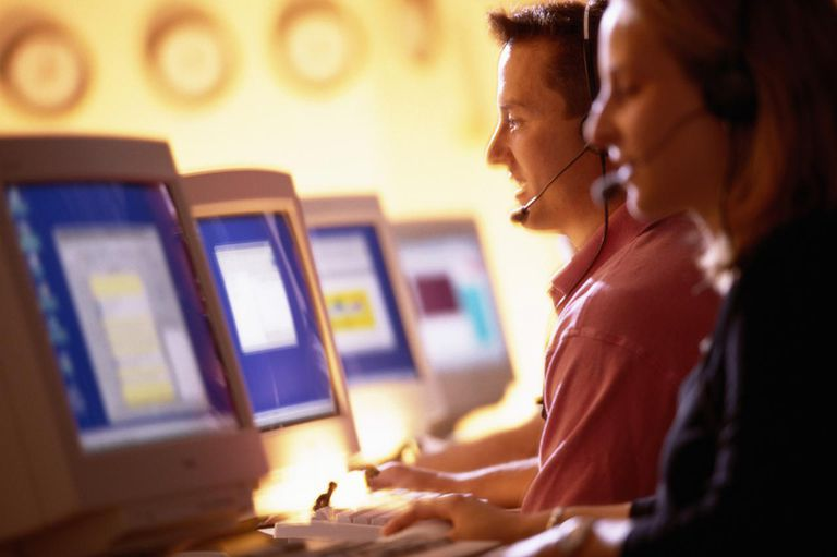 Telecommunications operators with headsets, in front of computers