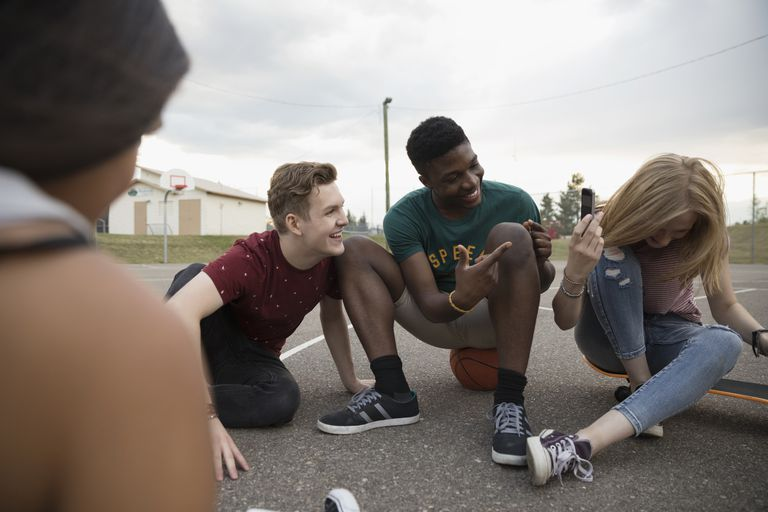 Teenage friends hanging out on outdoor basketball court