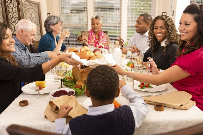 A family smiling during Thanksgiving dinner.