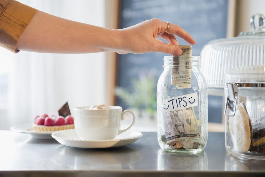 Woman putting money into tips jar.