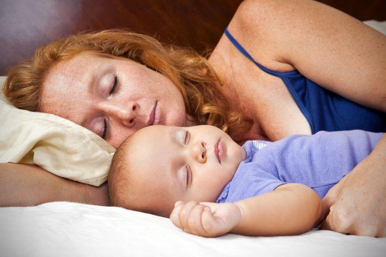 Woman sleeping with her baby sleeping beside her