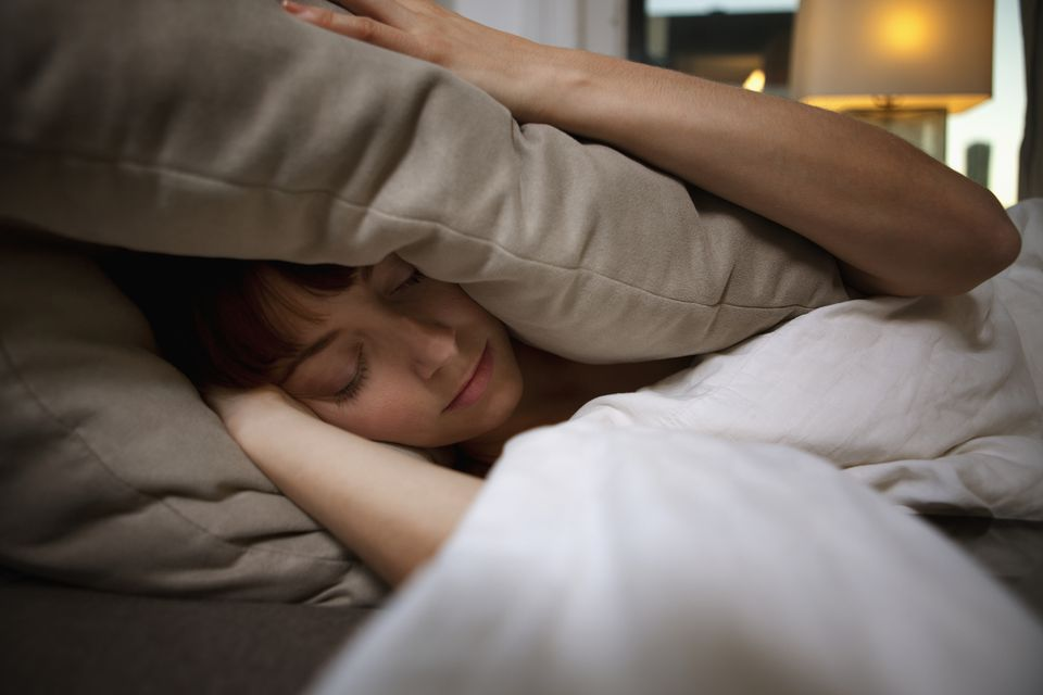 Woman unable to sleep covering ears with pillow