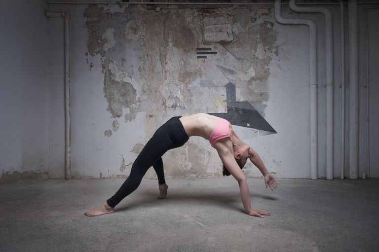Woman doing yoga pose called wild thing.