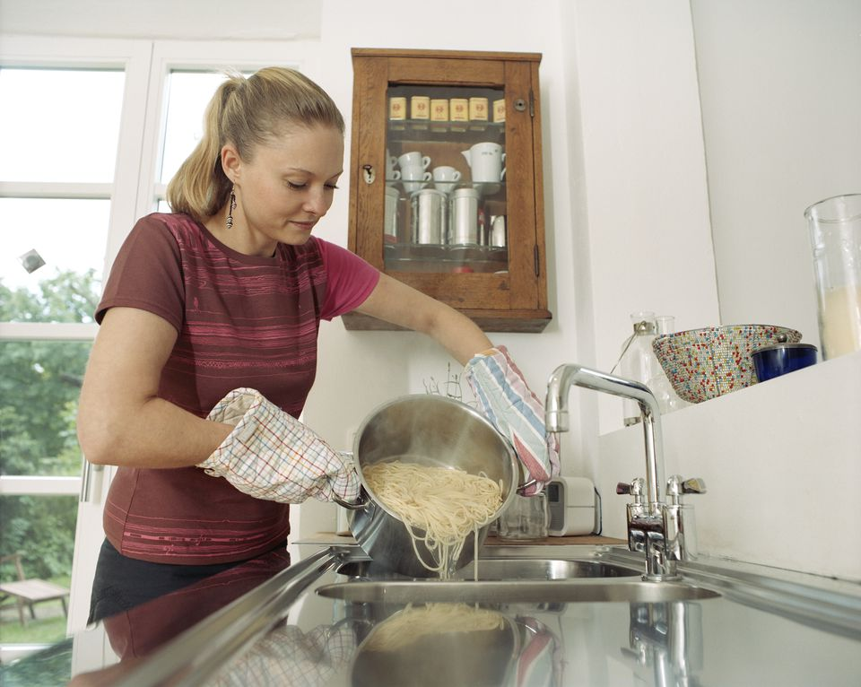 Young woman straining spaghetti over kitchen sink