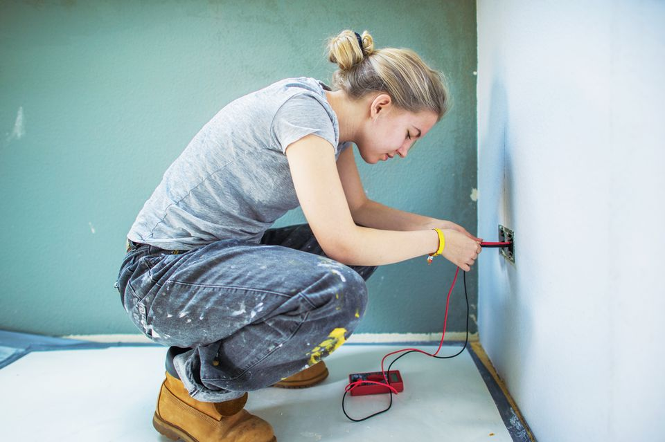 Young woman checking outlet with multimeter