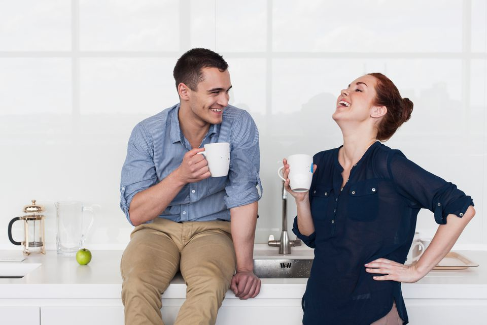 Man and woman enjoying coffee in the office kitchen