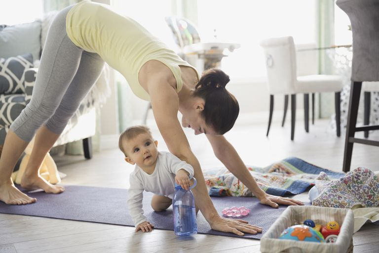 Mother practicing yoga by baby at home