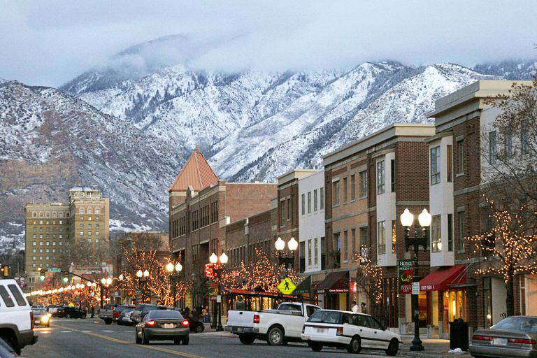 Buildings and cars on a street with christmas lights on trees in front of snowy mountains in Utah