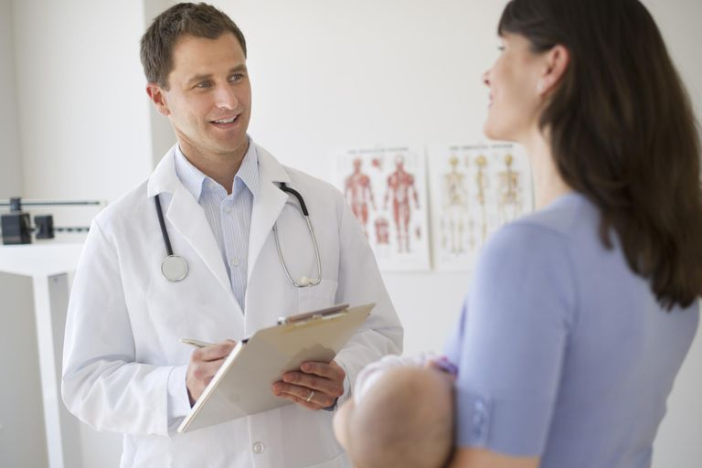 Doctor talking to woman in examination room.