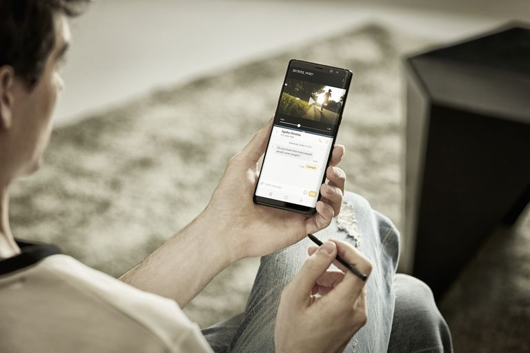 Man holding a Samsung phone and a stylus