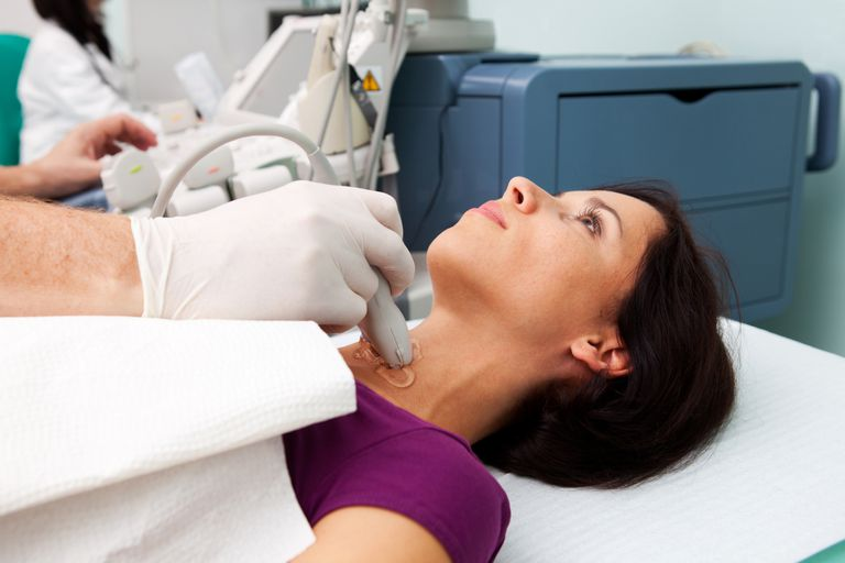 Doctor using ultrasound of patient's thyroid gland