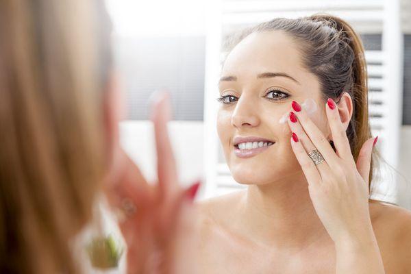 Woman spreading cream on face.