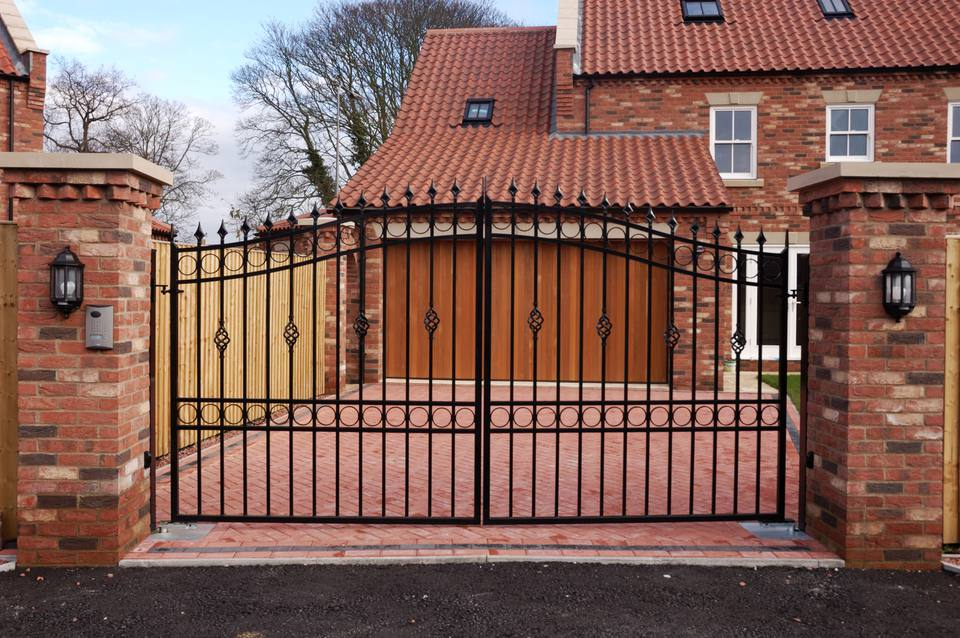 Wrought iron gate for a brick driveway.
