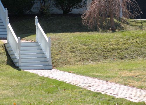 Photo of brick walkway up a hill, punctuated by steps.