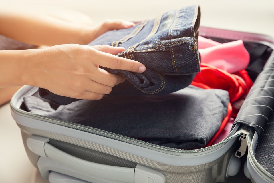 Cropped Image Of Hands Packing Suitcase