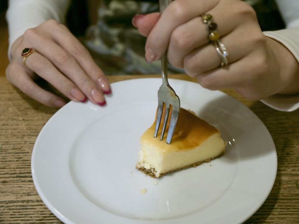 Woman eating a slice of cheesecake