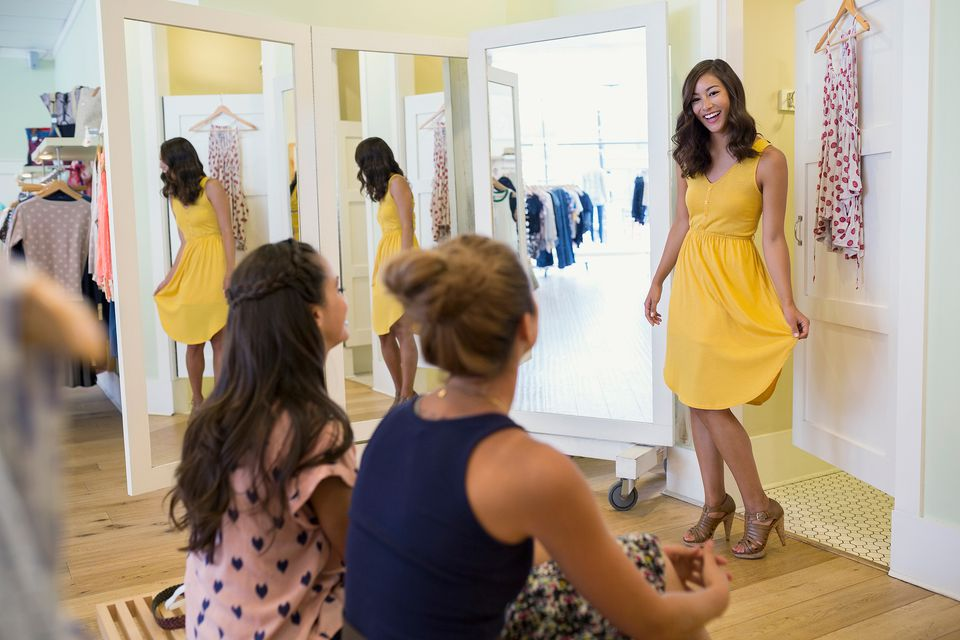 Woman trying on dress in boutique