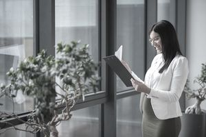 Pregnant businesswoman looking at documents in office lobby