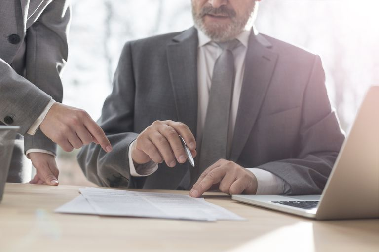 Secretary showing businessman where to sign document