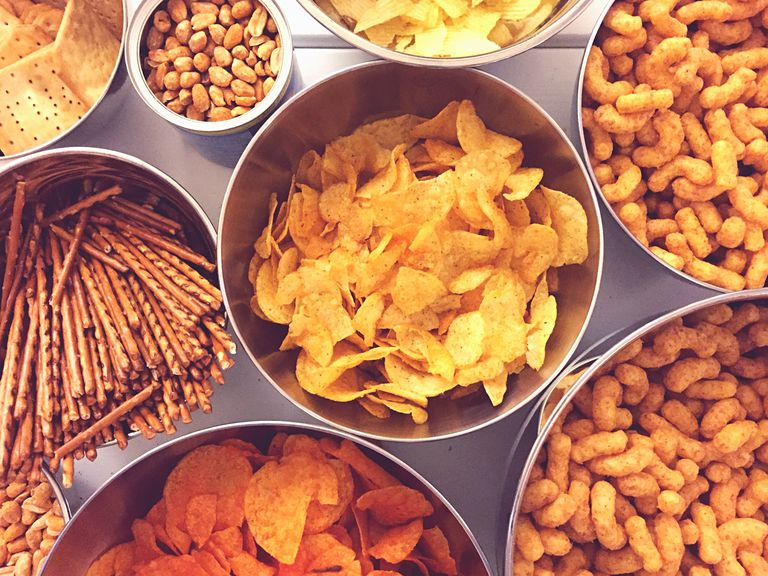 Bowls of chips and cheese curls and other crunchy snack foods