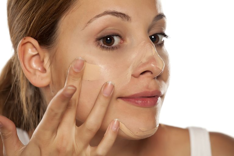 young beautiful woman applying foundation on her face