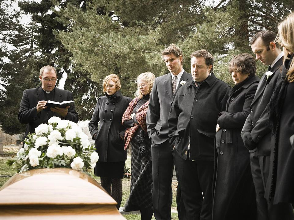 Mourners standing around a casket at a funeral