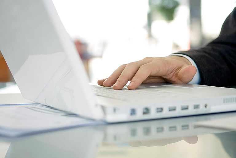 Close-up of a businessman's hand using a laptop