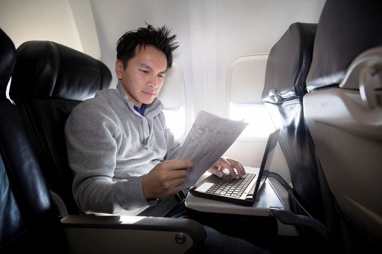 Young Asian man using laptop and reading newspaper on plane