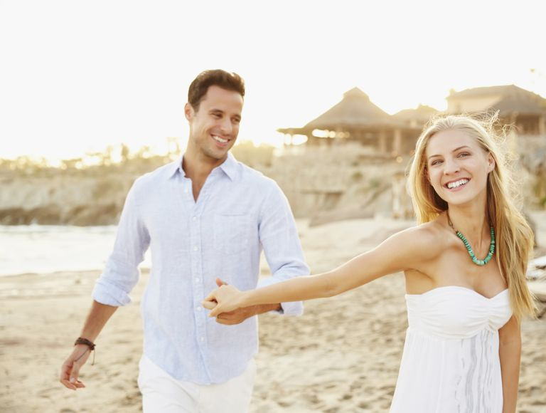 Newlywed couple holding hands on the beach